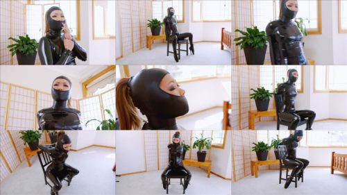 Mina is padlocked into a stiff collar wears a black shiny catsuit to chair bound with leather Gwen hood