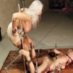 Steel Bondage - Ballgaged Gagged Sandra Silvers and Whitney Morgan are shackled to a steel pipe device on a wooden - Predicament and Wand Orgasm Endurance