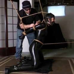 Fantastic Masha is roped up in a kneeling position in skintight black pvc catsuit - Captive in the Basement Dungeon - Rope bondage