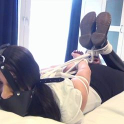 Hogtied on the bed - Paula is tightly hogtied with ropes and wearing pair of Dr Martens boots - Rope bondage