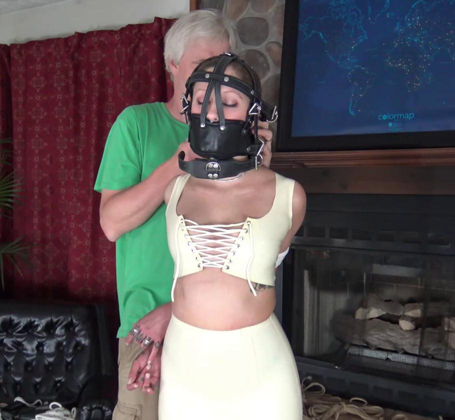 Isean is bound and with a leather muzzle – White Latex Predicament - Rope bondage