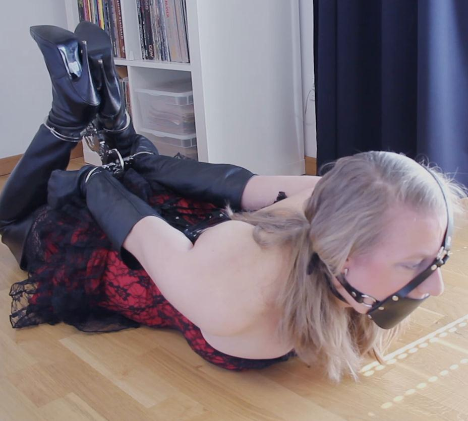 Strict bondage - Dina is hogtied and cuffed with three pairs of handcuffs into leather thighboots - This position is painful