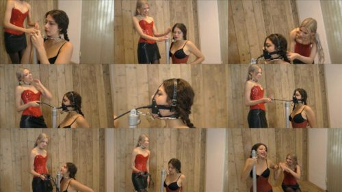 Female bondage - Vanessa and Julia Green – Vanessa is attached to the pillory and handcuffed - Pumpgag 2