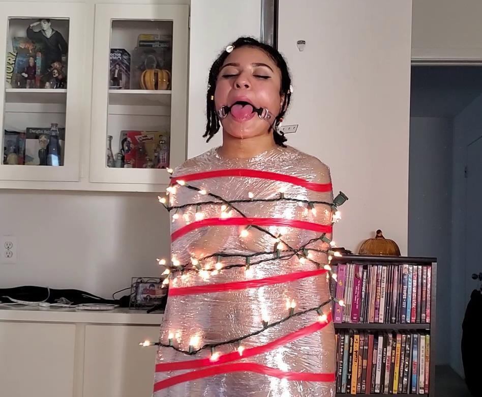 Jayda Blaze Mummified to a Pole – O Cum All Ye Faithful - Beautiful African American is bound with clear plastic wrap