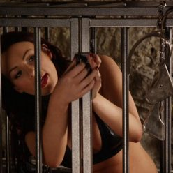 Photo of cuffed Penny Lee in cage
