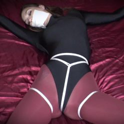 Photo of helpless Rocky Emerson with leather cuffs in leotard bondage